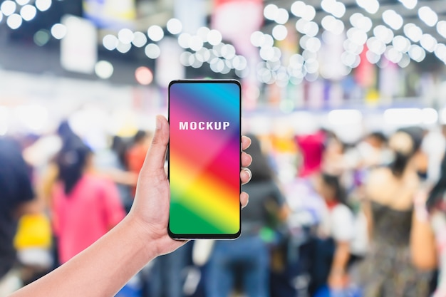 Mobile phone with blurred crowd of people in the shopping store Premium Psd