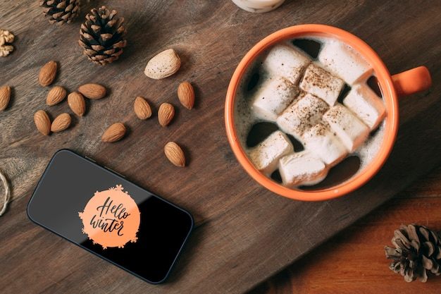 Mobile phone with hello winter and delicious winter drink Free Psd
