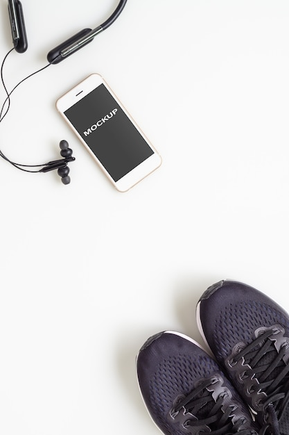 Mobilephone with bluetooth earphone and running shoes on white background Premium Psd