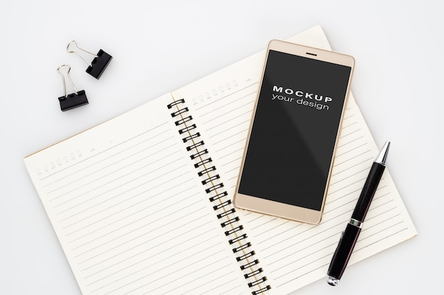 Mock up blank screen of smartphone on notebook with pen on white Premium Psd