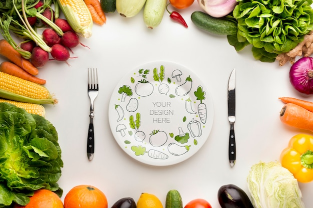 Mock-up and cutlery with frame made from delicious fresh veggies Free Psd