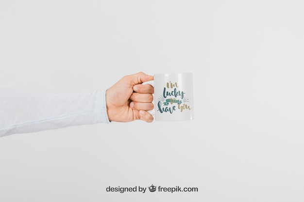 Mock up design of hand with mug Free Psd