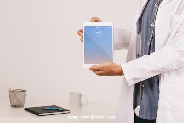 Макет дизайна с руки врача, держащего планшет Бесплатные Psd