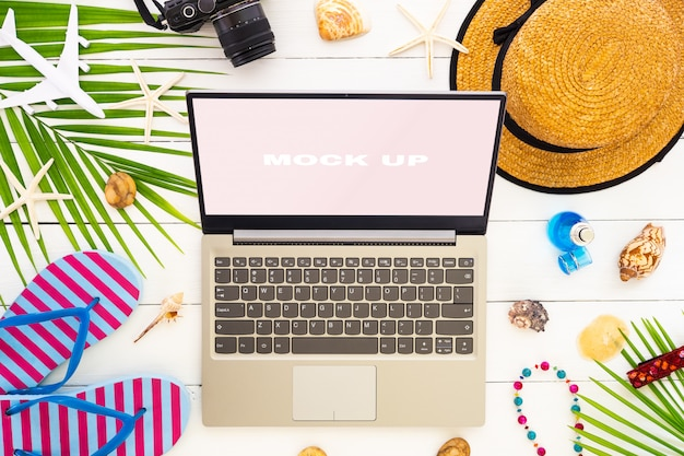 Mock up display of laptop on white wooden table for summer holiday vacation Premium Psd
