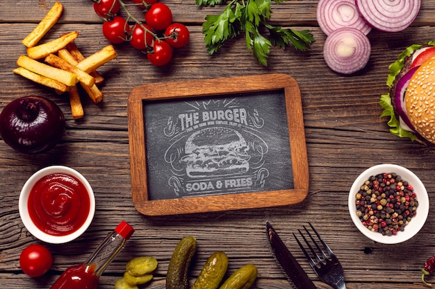 Mock-up frame surrounded by burger and ingredients wooden background Free Psd