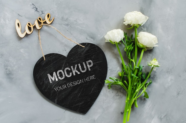 Mock up of greeting card. empty chalk board heart shaped with flowers and inscription love. Premium Psd