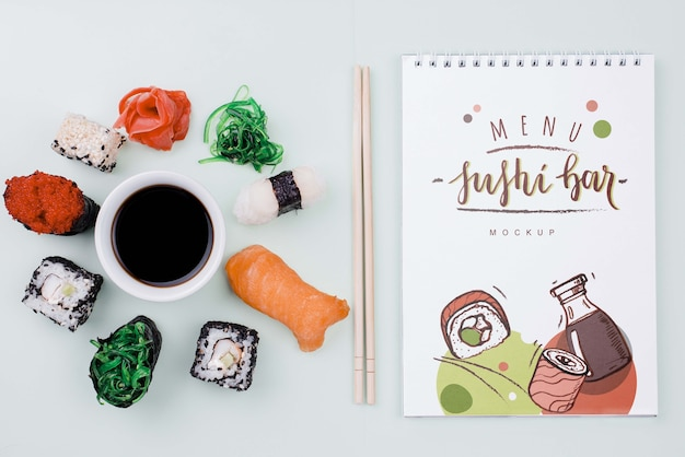 Mock-up sushi rolls with soya sauce and notebook Free Psd