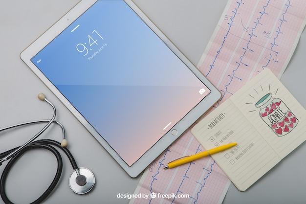Макет с планшетом, стетоскопом, кардиограммой и ноутбуком Бесплатные Psd