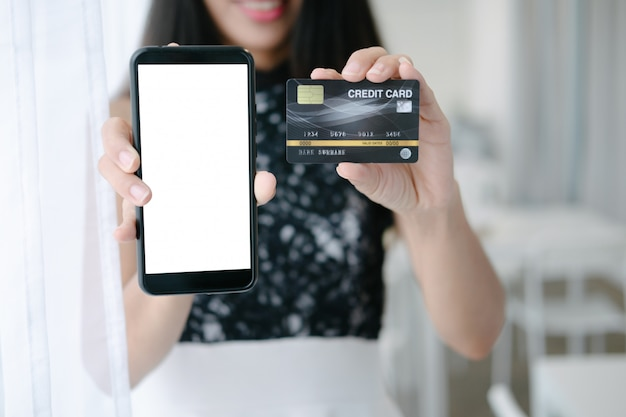 Mockup of beautiful woman holding credit card shopping online with smartphone on online websites Premium Psd