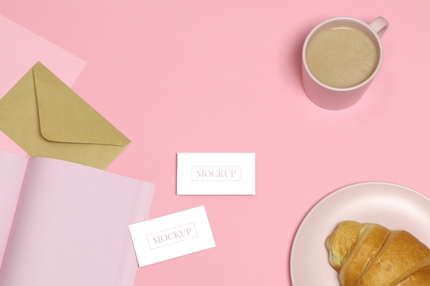 Mockup business cards on pink table with cup and cake Premium Psd