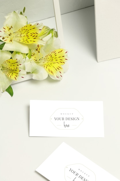Mockup business cards on white background, fresh flowers and frame Premium Psd