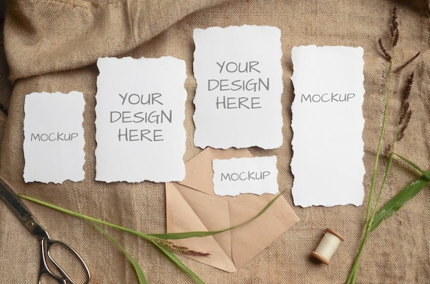 Mockup card greeting card or wedding invitation with jagged edges with herbs, vintage spool on a beige space from burlap fabric Premium Psd