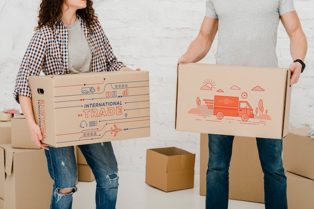 Mockup of couple with cardboard boxes Free Psd