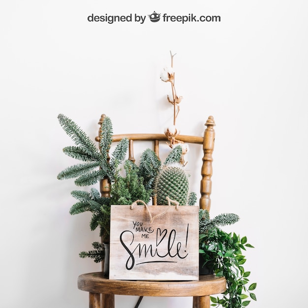 Mockup of frame on chair with flowers and cactus Free Psd