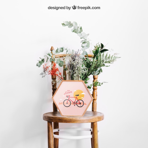Mockup of frame on chair with flowers Free Psd