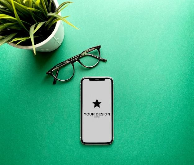 식물과 안경 녹색 배경에 모형 아이폰 11 프리미엄 PSD 파일