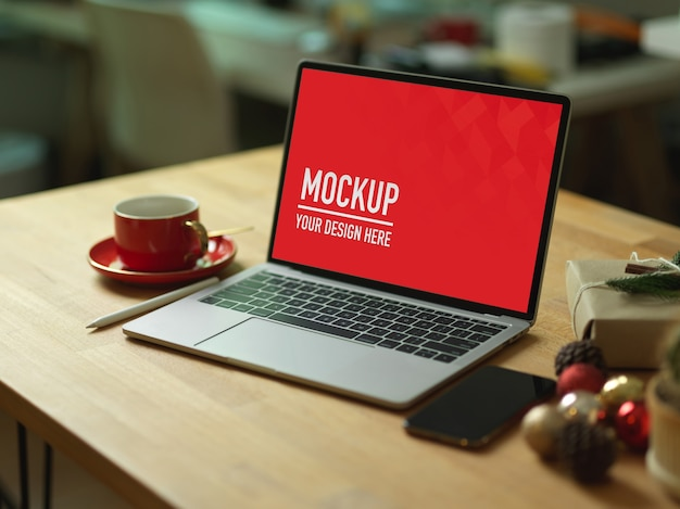 Mockup laptop on wooden table with smartphone Premium Psd