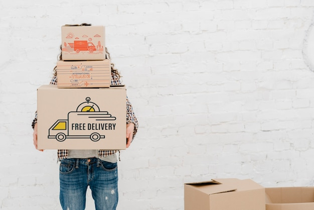 Mockup of man with cardboard boxes Free Psd