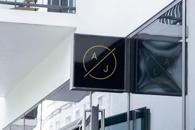 Mockup Of Modern Black Square Hanging Logo Sign On Corporate Building Facade Or Storefront