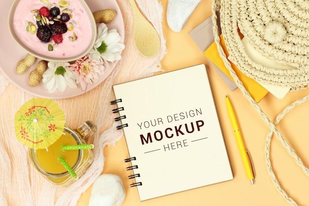 Mockup notes with straw bag, orange juice and dessert Premium Psd