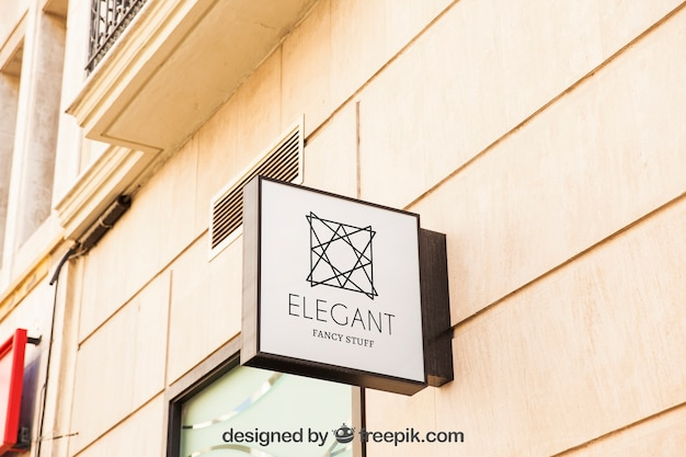 Mockup of white shop sign on city wall Free Psd