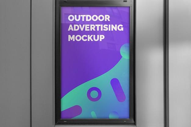 Mockup of outdoor vertical advertising in black frame window on grey facade Premium Psd