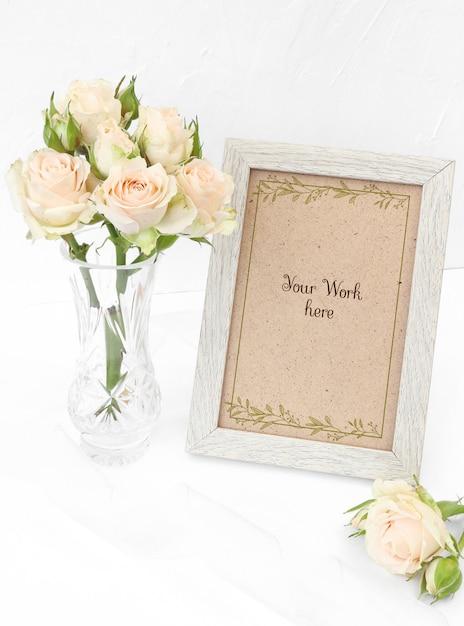 Mockup photo frame with beige roses in vase Premium Psd