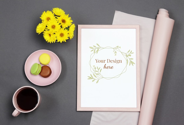 Mockup photo frame with yellow bouquet, cup of coffee and macaron on black background Premium Psd