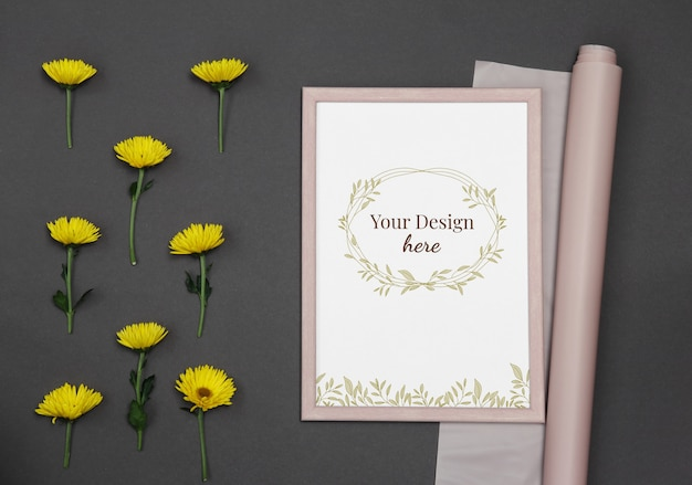Mockup photo frame with yellow flowers and pink paper on dark background Premium Psd