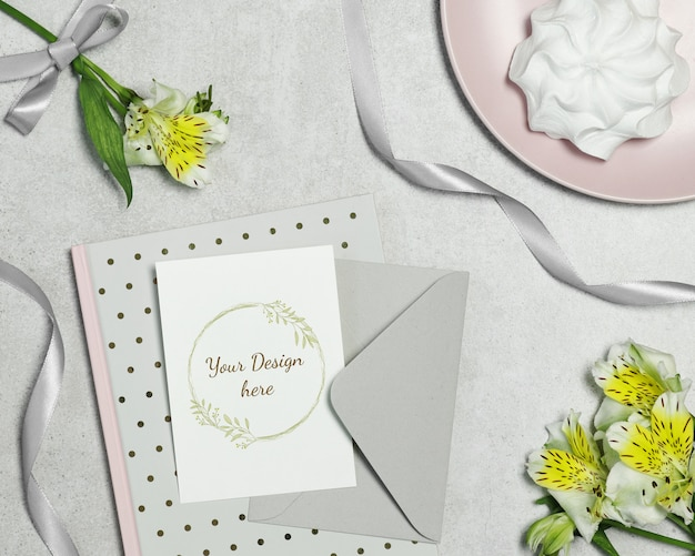 Mockup postcard on grey background with flowers, cake and ribbon Premium Psd