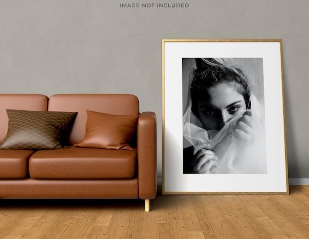 Рамка плаката макета в пустой деревянной раме, стоящей на современном интерьере гостиной. Бесплатные Psd