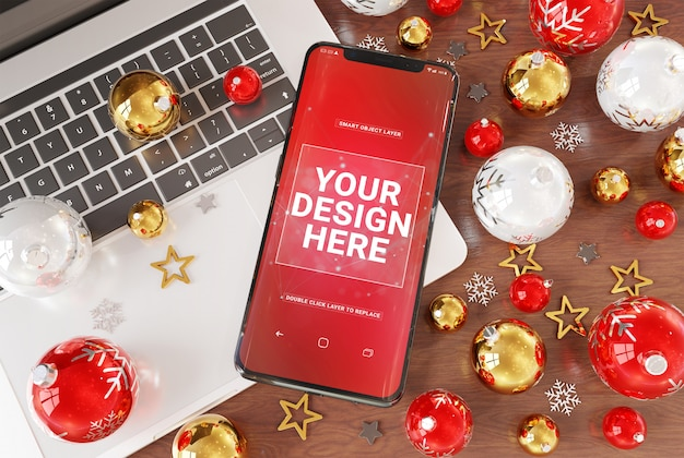 A mockup of smartphone on desktop with laptop and christmas baubles Premium Psd