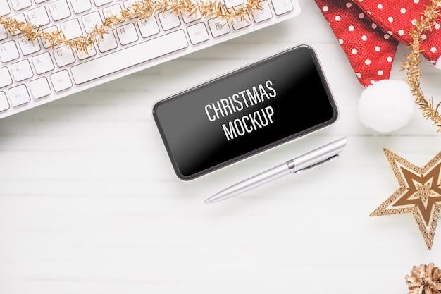 クリスマスと新年のホームオフィスの机の上のモックアップスマートフォン Premium Psd