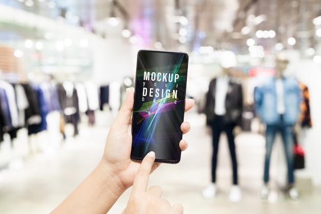 Макет смартфона с размытым магазином мужской одежды Premium Psd