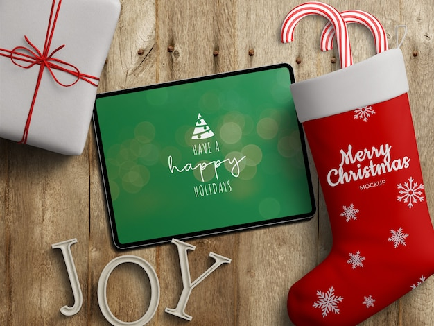 Mockup of tablet screen and stocking sock with christmas decoration on wooden table Premium Psd