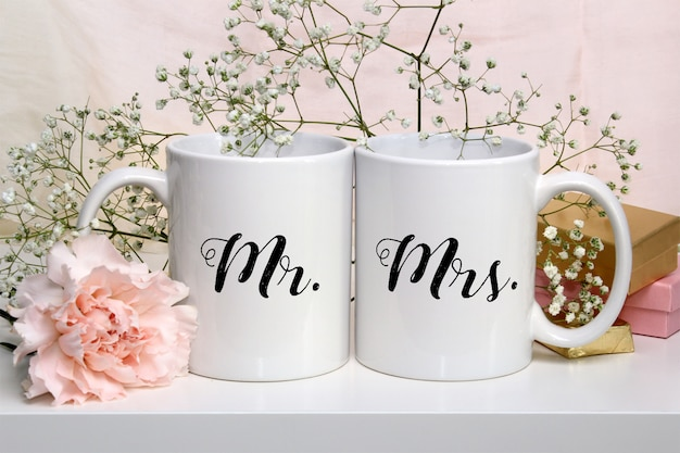 Mockup of two white coffee mugs with flowers Premium Psd