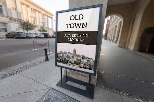 Mockup of vertical outdoor classic black metallic advertising frame stand on old town pavement Premium Psd