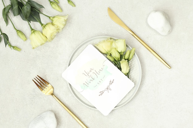 Mockup wedding card with flowers and gold cutlery Premium Psd