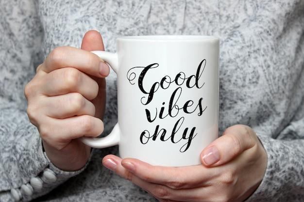 Mockup of a white ceramic coffee mug in woman's hand Premium Psd