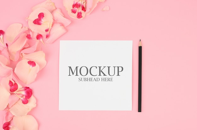 Mockup of white paper and pink flowers on a pink background Premium Psd