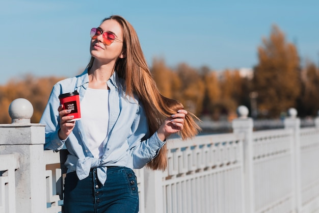 Modern blonde girl holding a cup of coffee mock-up Free Psd