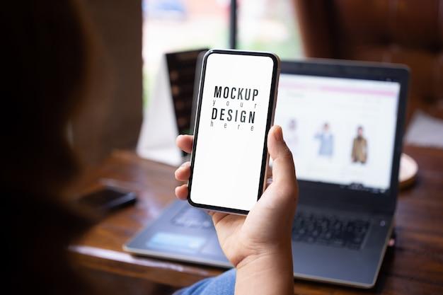 Mokcup мобильный телефон. персона держа и используя smartphone и компьтер-книжку нерезкости на деревянном столе в кафе. Premium Psd