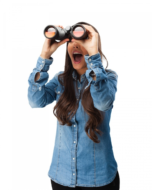 Nosy young woman with binoculars Free Psd