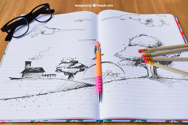 Notebook with drawing of landscape, pencils and glasses Free Psd