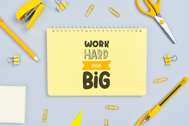 Notebook with positive message and office tools beside Free Psd