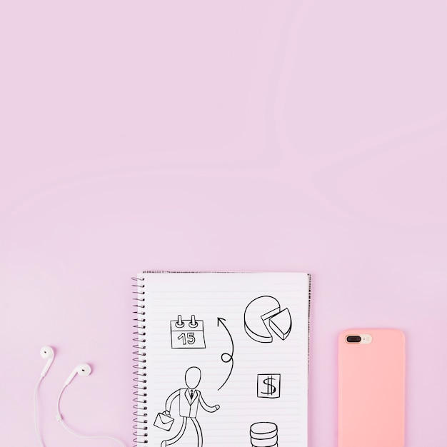 Notepad mockup next to smartphone and earphones Free Psd