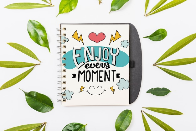 Notepad mockup with tropical leaves Free Psd