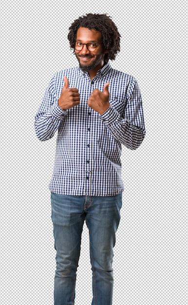 ハンサムなビジネスアフリカ系アメリカ人の男は陽気で興奮して、笑顔と彼女の親指を上げる、成功と承認、okのジェスチャーの概念 Premium Psd
