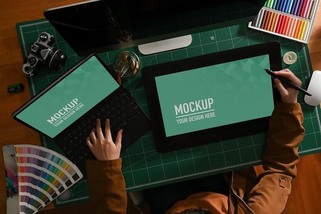 Верхний снимок девушки-графического дизайнера, работающей с макетом планшета и ноутбука на компьютерном столе Premium Psd