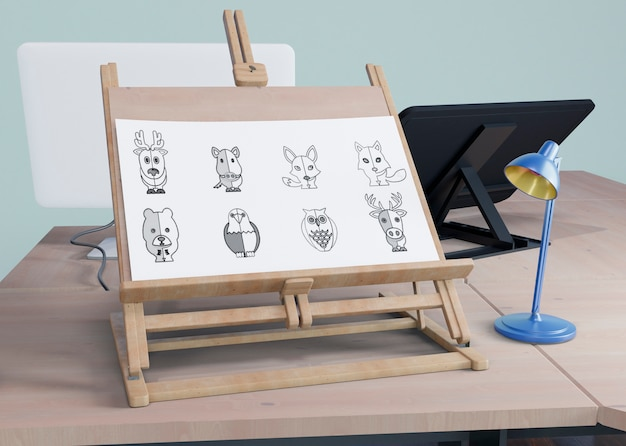 Painting support on desk with lamp beside Free Psd